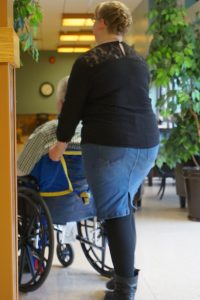 Immediate Volunteer Needs - Volunteer pushing a resident in a wheelchair